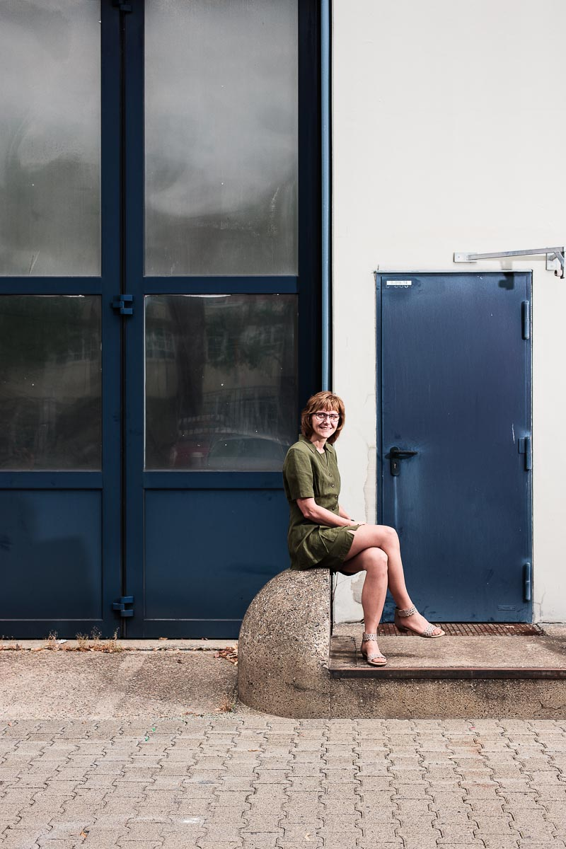 Portrait Margit Stefaniak sitzend vor einer Wartungshalle im Betriebshof der BSR in Berlin