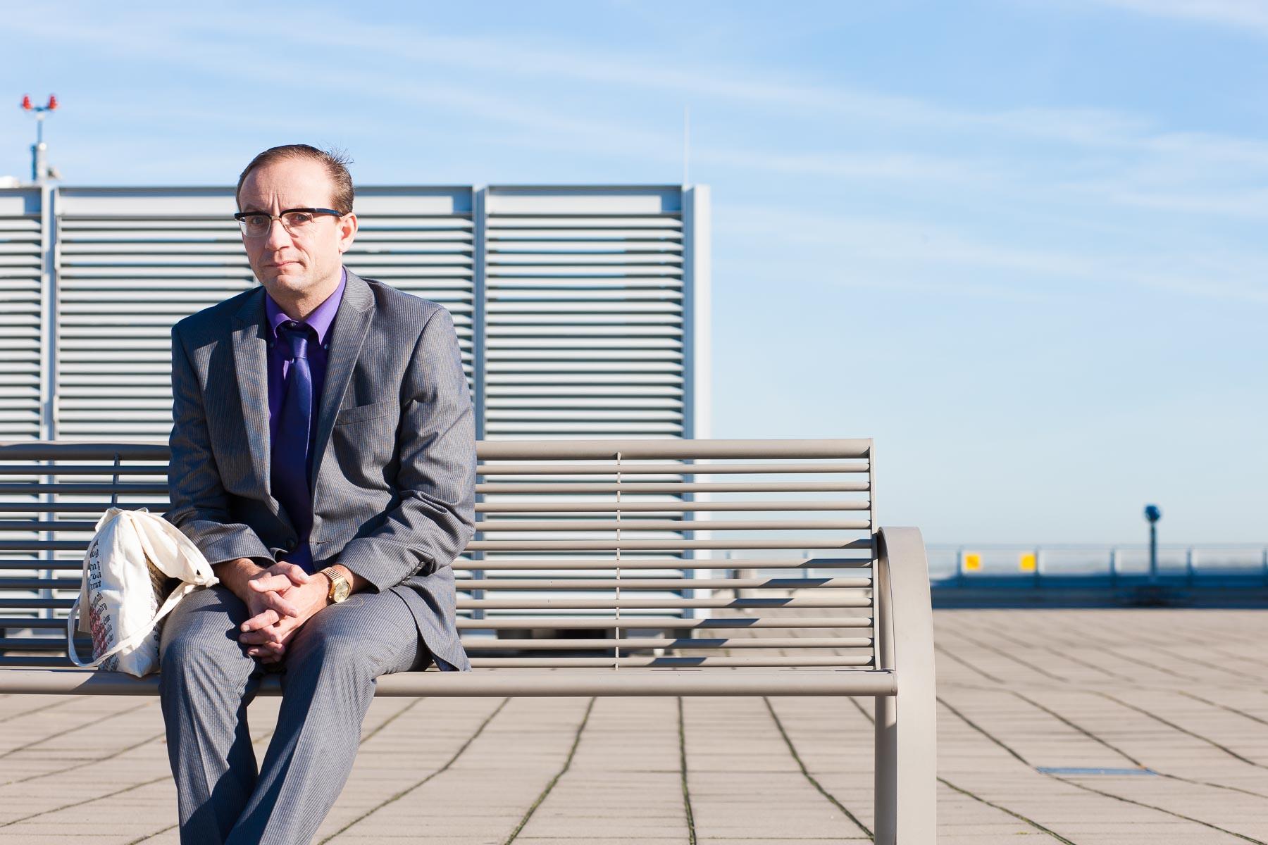 Wigald Boning sitzt auf einer Bank am Flughafen