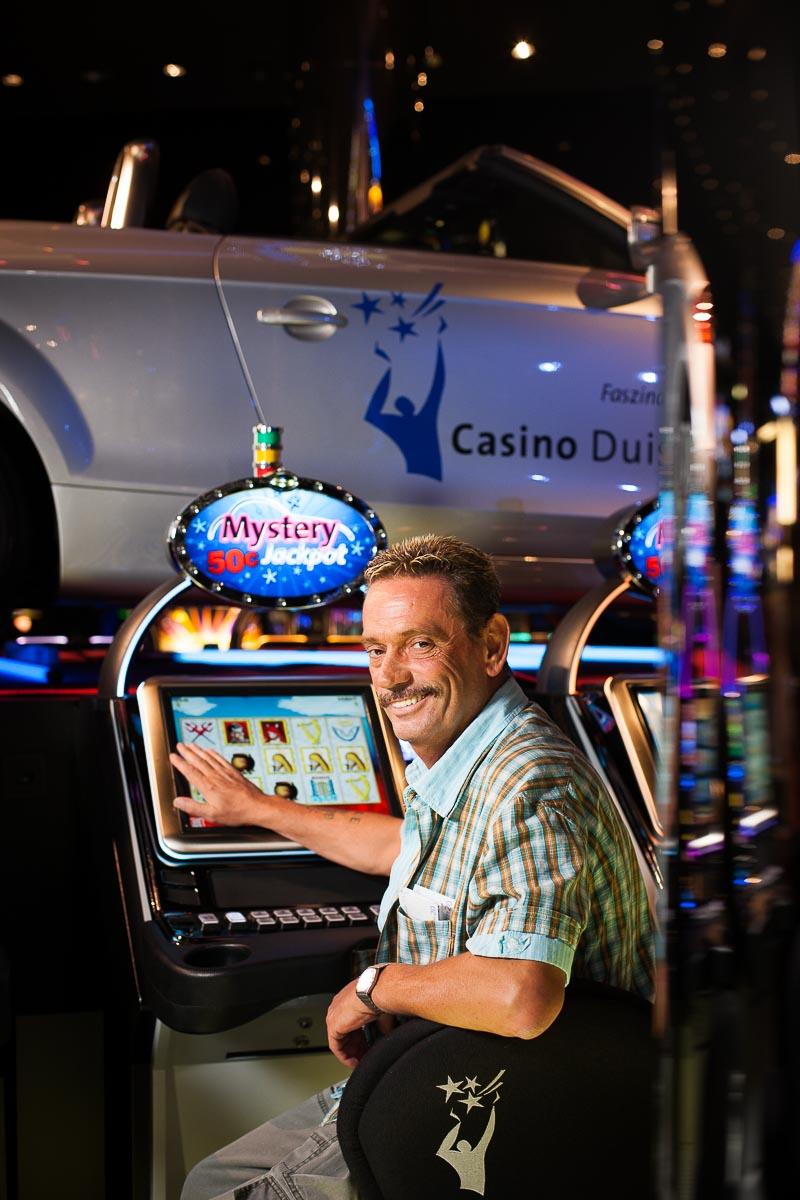 Eine Person sitzt an einem Geldspielautomaten in einem Casino in Duisburg