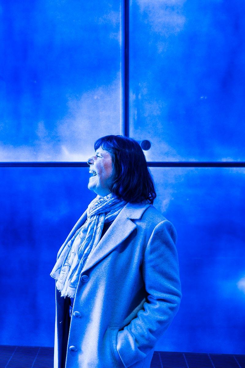 Frau Kocabiyik steht vor blauem Hintergrund in einer Kirche in Essen